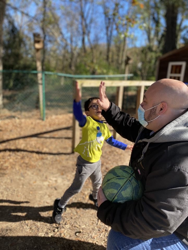 Male ECE Teacher providing young child high five.