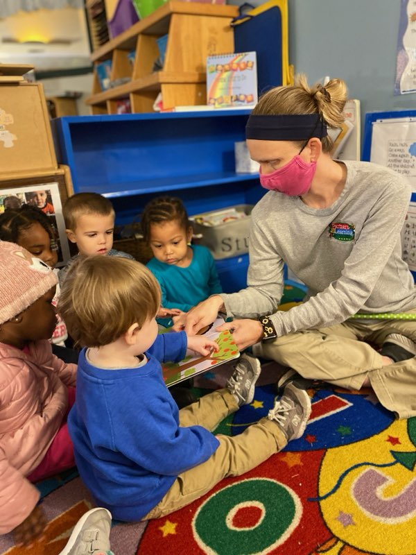 ECE teacher reading book to toddlers